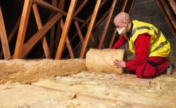 Man unrolling loft insulation